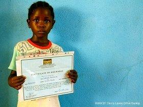 エボラ出血熱で両親を失ったという孤児。手には自身の回復証明証(提供:(公財)日本ユニセフ協会)