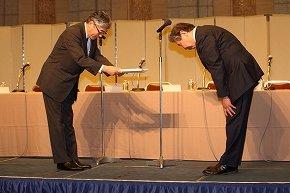 第三者委員会の中込秀樹委員長(右)から報告書を受け取る朝日新聞社の渡辺雅隆社長(左)