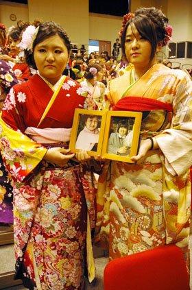 小松彬乃さんとその母志知子さんの遺影を抱いた藤田晴香さん(左)と飛田槙惟さん(右)=2014年1月12日、大槌町内の城山公園体育館