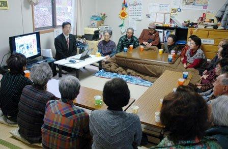 「お茶っこの会」では碇川豊町長がパソコンをテレビにつないで復興状況を説明し質疑を交わします=2013年11月25日、大槌第3仮設団地談話室