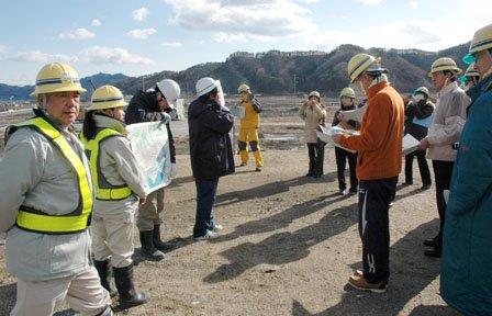 町方地区の先行盛り土の上で見学者に復興計画を説明する工事関係者=2014年2月7日