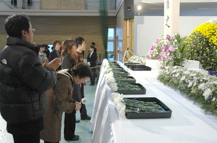 追悼式で献花する参列者=2014年3月11日、大槌町役場多目的会議室