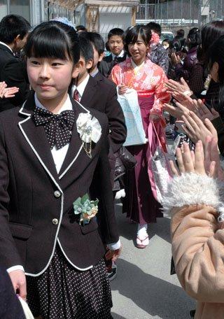大槌小学校の卒業式を終えて在校生に拍手で送られる児童たち=2014年3月19日、大槌町の大槌小