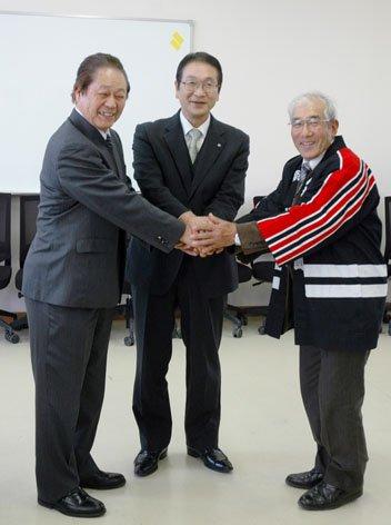 退任式を終えて握手する左から煙山佳成さん、碇川豊町長、4月1日から新団長になった越田雅美さん=2014年3月31日、大槌町役場