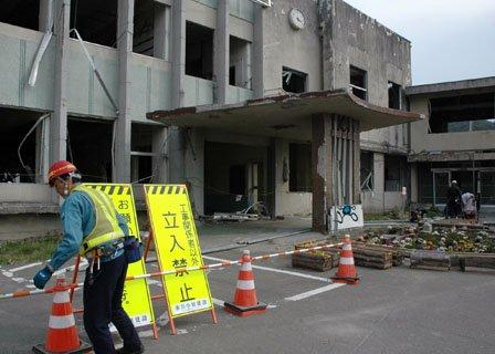 解体工事のために仮囲いの準備をする作業員=2014年4月10日、大槌町の旧役場庁舎