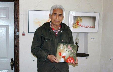 展示されている原画を前に絵本を手にする佐々木格さん=2014年4月20日、大槌町吉里吉里