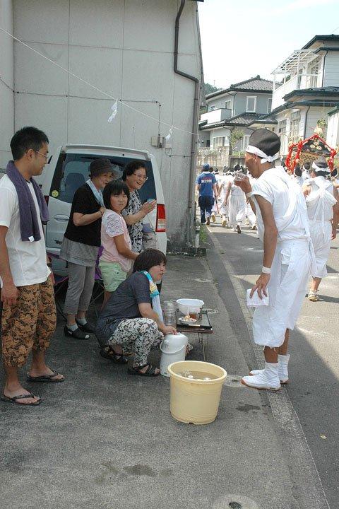 沿道では地元の人たちが手を合わせて神輿を迎えます=2014年8月24日、大槌町吉里吉里