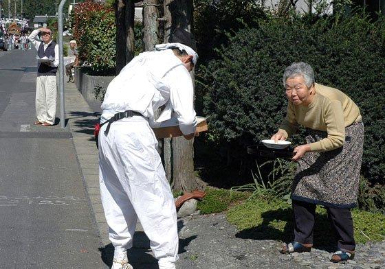 神輿を迎えた人たちは神輿がまく塩を用意し手渡しました=2014年9月21日、大槌町