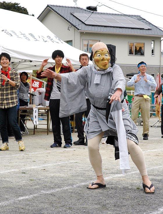 踊りにはひょっとこの面をつけた男性が飛び入りしました=2014年10月5日、大槌町の吉里吉里小学校校庭