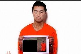 ユーチューブで公開された後藤健二さんの写真。湯川遥菜さんの写真が印刷されたパネルを持っている(画像を一部修整しています)