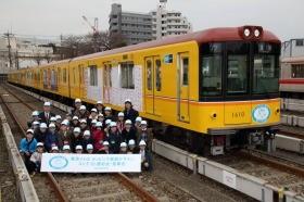 入賞者はラッピング電車を背に記念撮影。5月末まで運行される