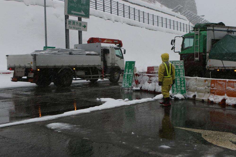 土樽PAのチェーン着脱場。係員が装着の有無をチェックしている。雪の中、黙々と誘導棒をふるう姿が印象的だった