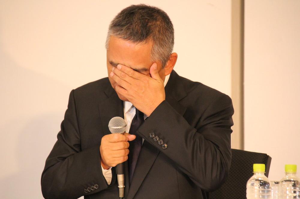 手で涙を拭う岡本社長