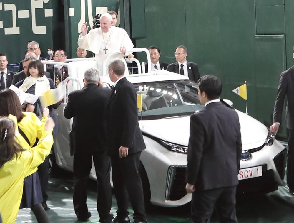 「パパモービレ」からミサ参列者の大歓声に応えるフランシスコ教皇。トヨタ自動車の燃料電池車(FCV)「MIRAI(ミライ)」をベースに製造された