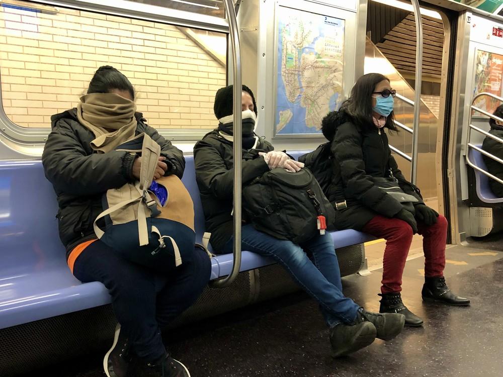 ニューヨークの地下鉄で、マスクやマフラーで顔を覆う乗客たち