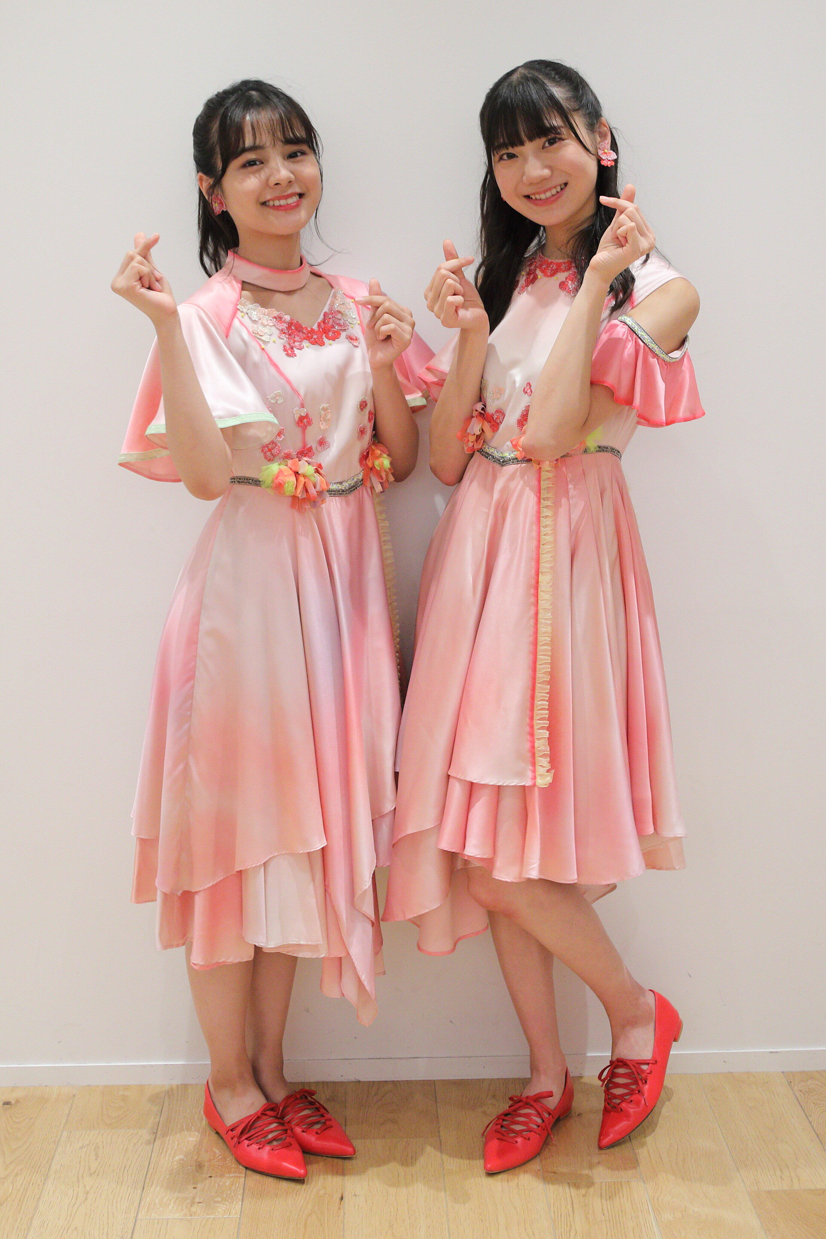 新曲「シャーベット」ピンクの衣装は、1期生(写真左・本間日陽さん)は首元が開いているデザインで、研究生(同右・藤崎未夢)は肩が開いているデザインだ
