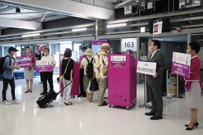 ゲートでは、係員らが「旅先での感染予防の徹底を!」などと書かれたパネルを持って乗客を見送った