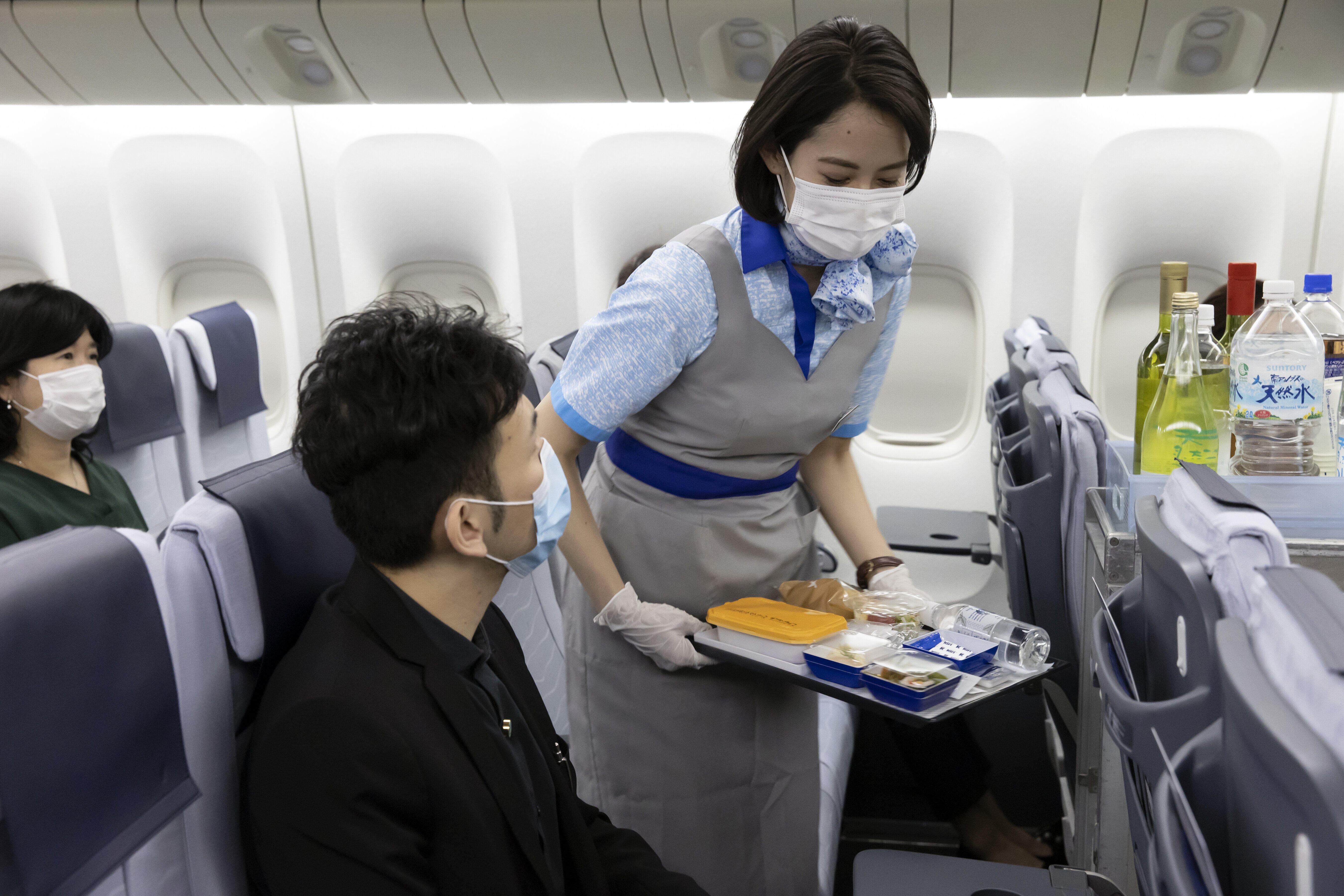 ANAの客室乗務員は機内でマスクとビニール手袋を着用し、機内食などをトレーに載せて提供している(ANA提供)