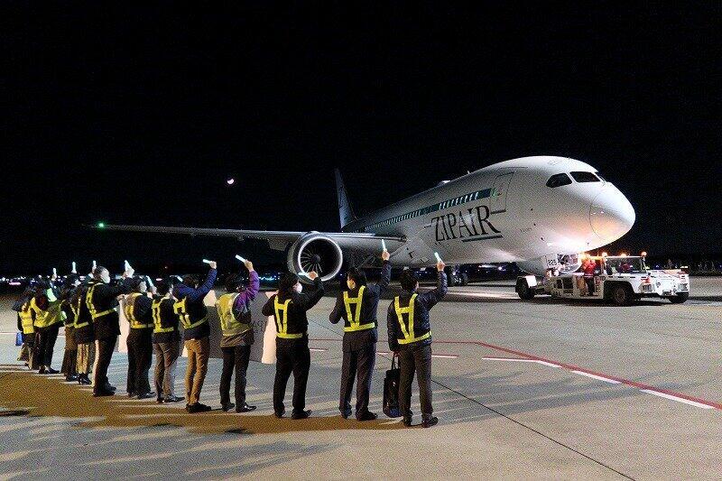 ZIPAIRのホノルル行き初便には乗客26人が搭乗した。空港係員がペンライトを持って見送った