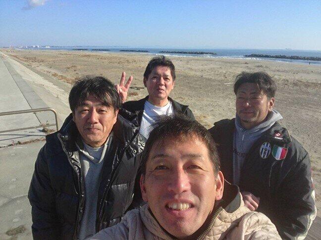 サーフィン後に仲間と写真におさまる前之濱博さん(中央手前)と末永薫さん(中央後方)=荒浜の海岸で2019年12月、前之濱さん提供