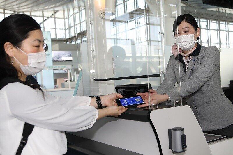実証実験に協力した乗客(左)が「コモンパス」で「デジタル陰性証明書」を空港係員に見せてチェックインした