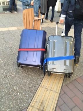 ご丁寧と言うか、斜めに倒したキャリーバッグまでが「カップル」である。(東京・池袋で)