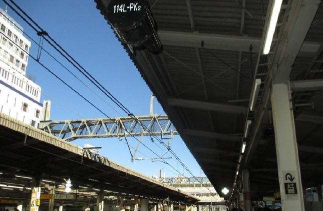 同じ駅でも、全部の蛍光灯をつけているホーム(向こう側)と、3本のうち2本を消しているホーム(手前)。(東京のJR池袋駅で)