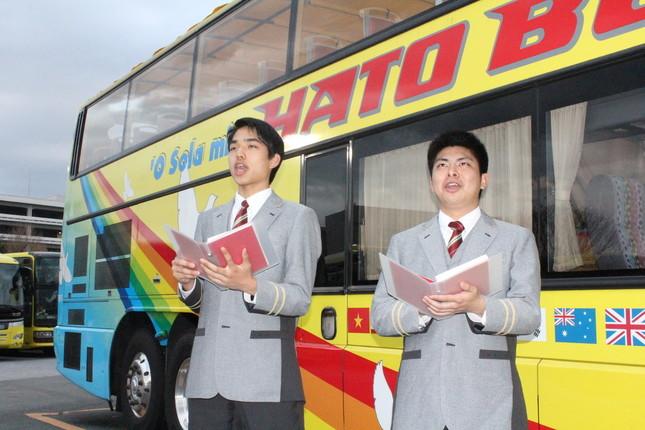 バスの前で発声練習をする三國蘭さん(左)と松尾龍治さん(東京・平和島のはとバス本社で)