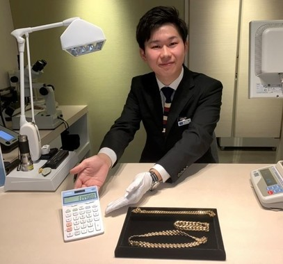 お客が持ち込んだ金の装飾品を査定する鑑定士(コメ兵銀座店で、石原健太郎氏撮影)
