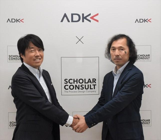 「ダーザインブランディング」の説明会で握手をかわすスコラ・コンサルトの辰巳代表(左)とプロジェクトリーダーを務めるADK MSの古村さん