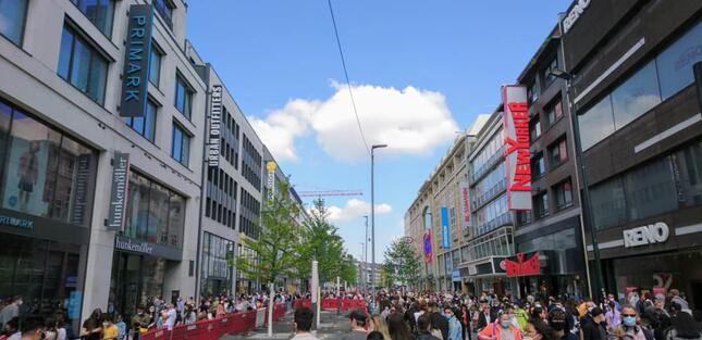 ショッピングを楽しむ人が歩道に溢れ、人数制限のため店舗前に長蛇の列ができる店舗もある