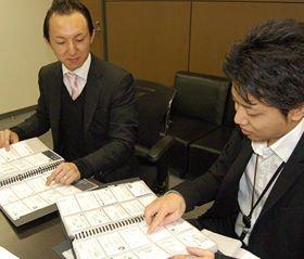 井手高志さん(左)は、学生メディアセクションの広報リーダー・梅田優さん(右)らと従来の名刺をチェックしながら、新しいデザインの構想を練った