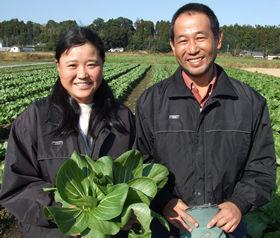 自分たちが育てた畑の前に立つ黒川剛さん・栄子さん夫婦。手にしているのは、チンゲンサイ