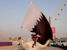 白装束のカタール人は国旗を持って応援