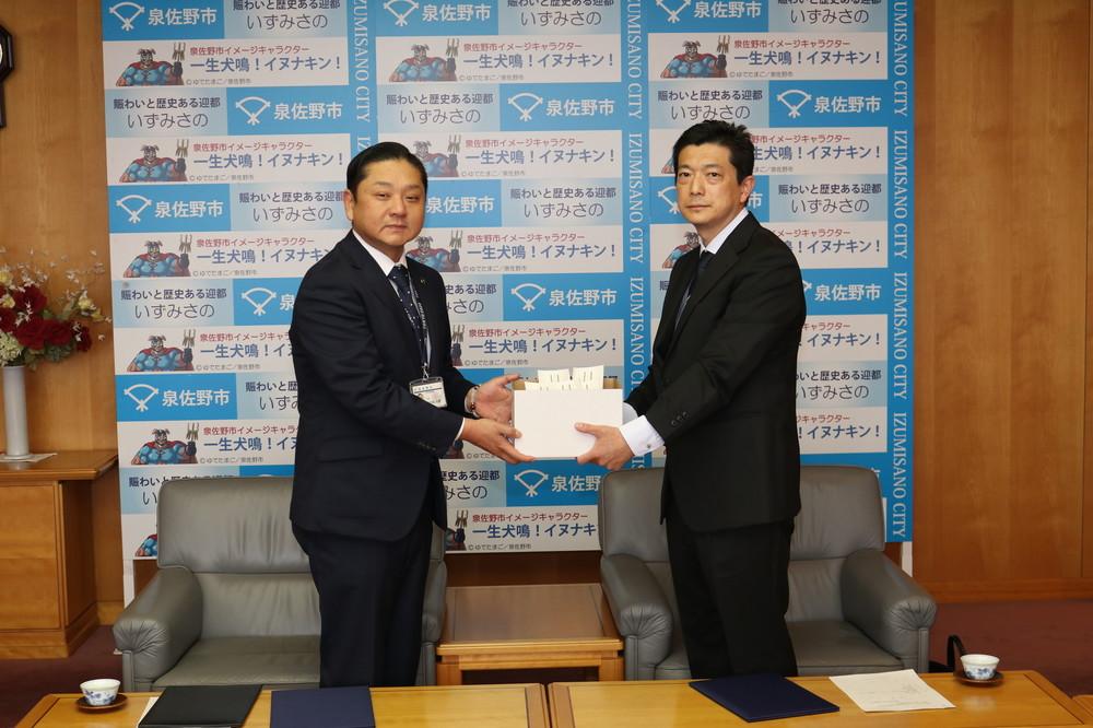 泉佐野市の千代松市長(左)と、りんくうメディカルクリニックの小村院長が調印式