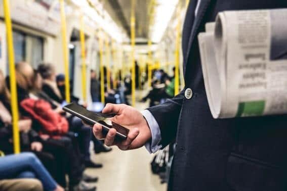 通勤中の電車内でスマホを操作する男性