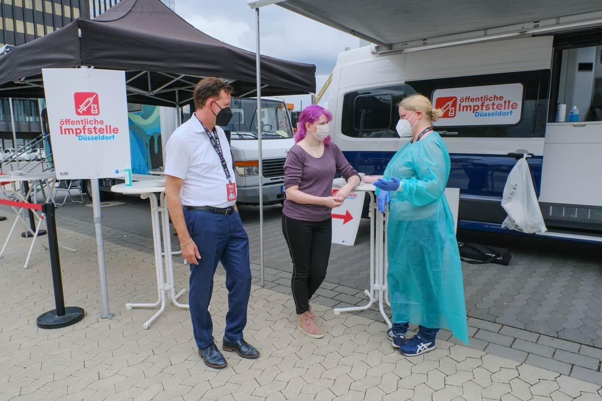 ドコミのワクチン会場を視察するデュッセルドルフ市ブルクハルト・ヒンチェ危機管理部長と、ドコミ参加者ケリー・ジンデマンさん、内科医のグニラ・エアドマンさん。(c)Landeshaupstadt Dusseldorf/Michael Gstettenbauer