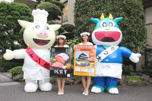 「まつり」キャンペーンのためJ-CASTニュースを訪れた東京食肉市場マスコットキャラクター、トン吉とモウ太、佐賀市観光キャンペーンレディの白井夏海さん(左)と木塚由梨絵さん。モウ太もトン吉も、木塚さんと白井さんも当日は会場で来場者をアテンドする
