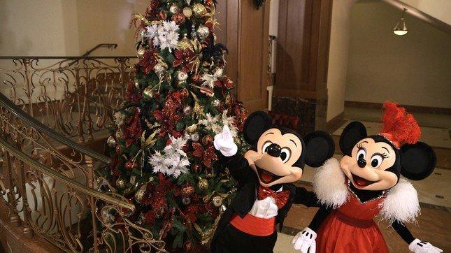 ツリーの傍らでクリスマスを楽しむミッキーとミニー(c)Disney