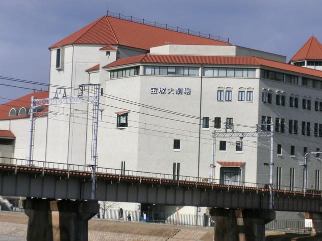 阪急今津線の軌道近くにある宝塚大劇場。建物背後に宝塚駅がある