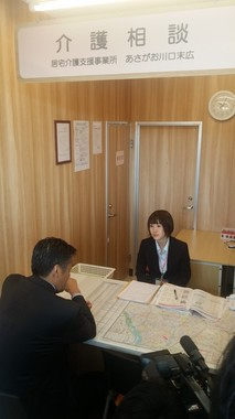 店内の居宅支援事業所カウンターで説明を聞くローソンの玉塚社長(左)