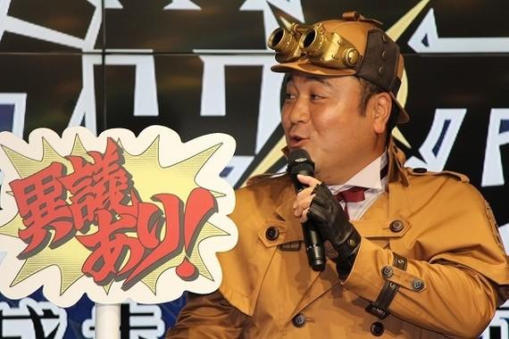 ゲームの決め台詞「異議あり!」のパネルを持つ山崎さん