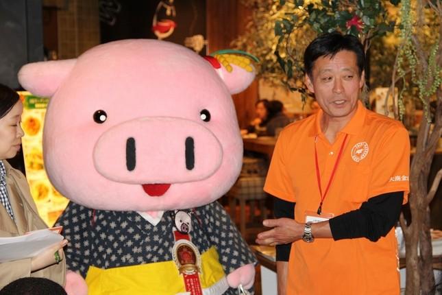 「きき豚」で出された「米の娘ぶた」生産者、大商金山牧場の矢口一寿さんと、マスコットの米の娘ちゃん