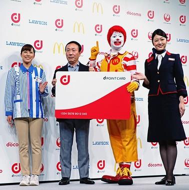 dポイントカードを模したパネルを掲げる、NTTドコモ加藤薫社長とドナルド・マクドナルド