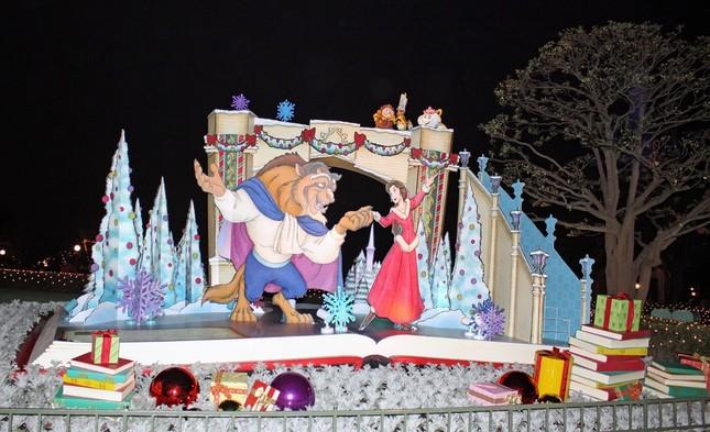 TDL、シンデレラ城前プラザに飾られた「美女野獣」のデコレーション。ベルとビーストがスケートを楽しんでいるシーンの周りにプレゼントの本などが置かれている