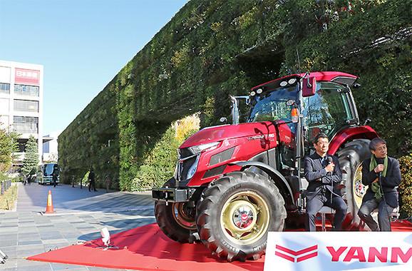 トラクターの後方の緑は、安藤さんが発案した巨大緑化モニュメント「希望の壁」