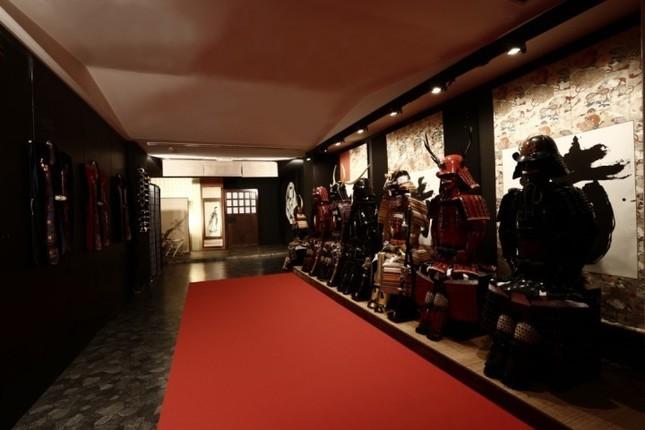 左手前に「陣羽織」、左奥に「刀」、右に「鎧」がそれぞれ展示されている