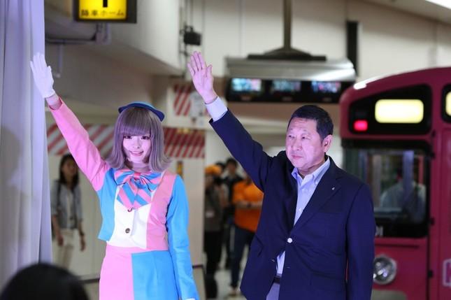 一番列車のセレモニーで右腕を上げる、きゃりーさんと西武鉄道の後藤高志取締役会長