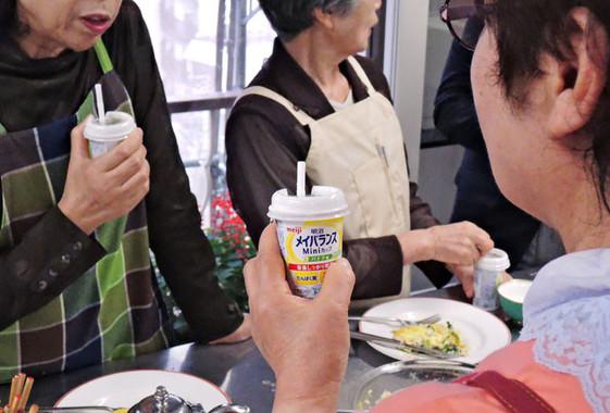 「明治メイバランスMiniカップ」を飲む生徒たち