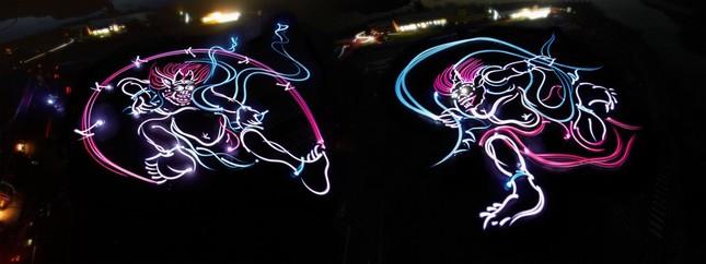 ライトで車体を照らしながら光の線を重ね巨大な風神・雷神を描く